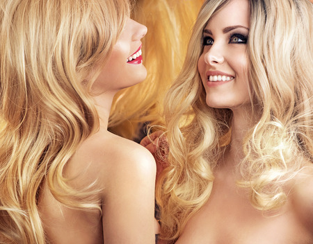 cabello rubio: Dos amigas rubia atractiva teniendo cuidado de su cabello