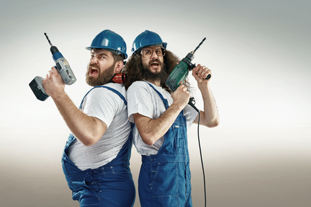 electrical contractor: Funny portrait of two cheerful craftsmen Stock Photo
