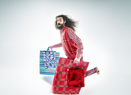 Nerdy guy holding a bunch of various shopping bags