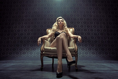 Dominating blond woman sitting on the vintage armchair
