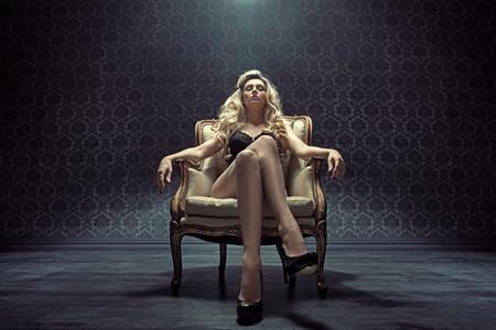 Dominiert blonde Frau auf dem Vintage Sessel sitzen