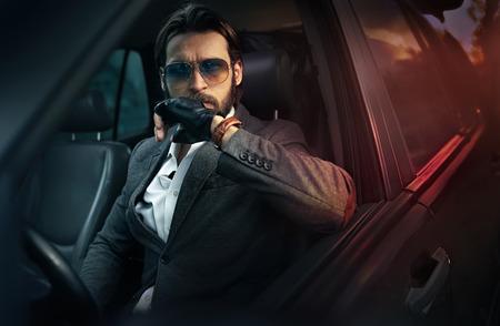 車を運転してハンサムなファッション男 写真素材