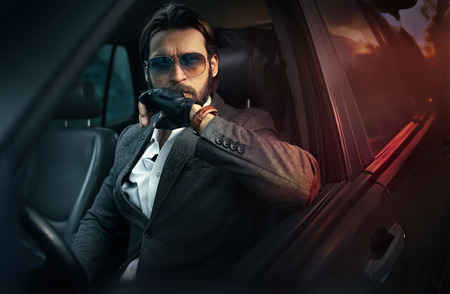Handsome fashion man driving a car