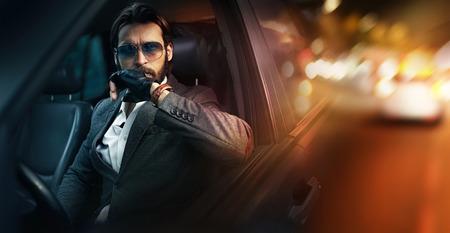 Openlucht portret van elegante man besturen van een auto Stockfoto