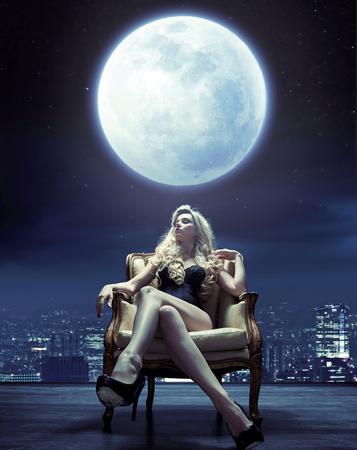 Sinnliche junge Frau, die unter dem Mondlicht sich entspannt