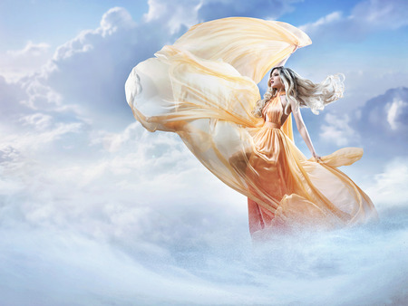 Dreamy image of a beautiful young woman in the clouds
