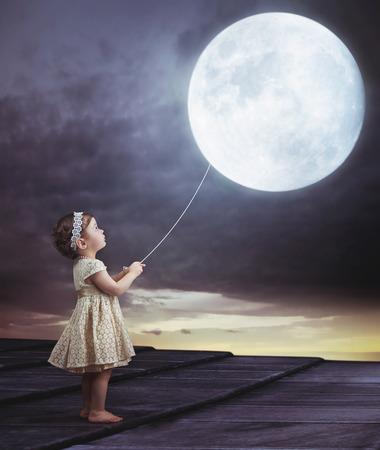 Fairy portait of a little cute girl with a moony balloon 스톡 콘텐츠