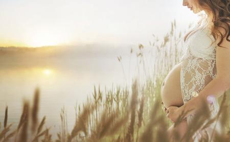 Mujer embarazada caminando en la pradera de verano fresco