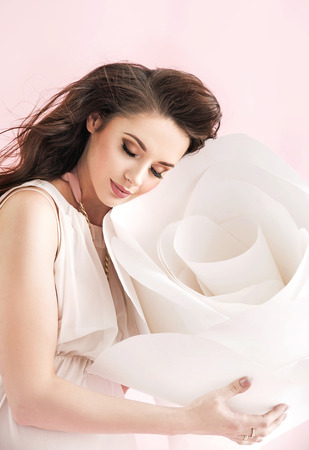 Concetpual image of brunette woman cuddling a white giant rose photo