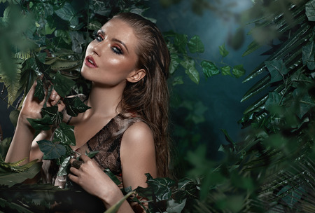 Portrait of beautiful woman posing in tropical forest photo