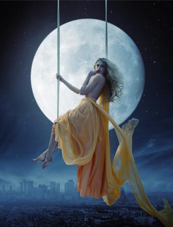 Elegante vrouw over grote maan achtergrond Stockfoto