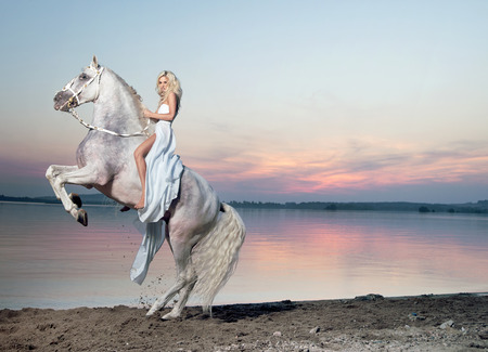 Portrait of a blond woman riding a majestic horse photo