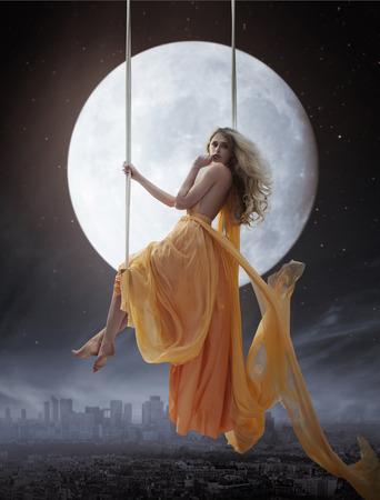 Elegante junge Frau, die über großen Mond Hintergrund
