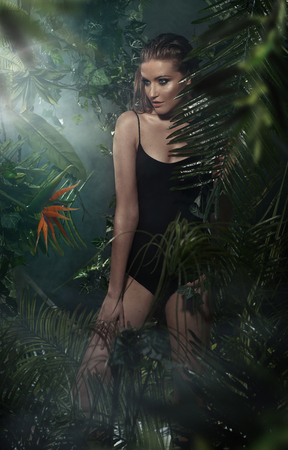 Beautiful young blond lady posing in tropical forest photo