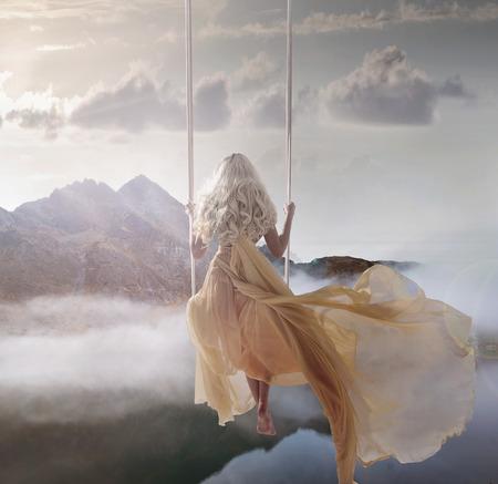 잔잔한 호수 위의 스윙에 앉아 매력적인 여자