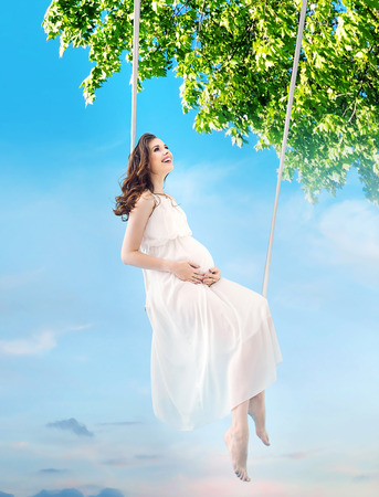 Pregnant lady sitting on the wooden seesaw