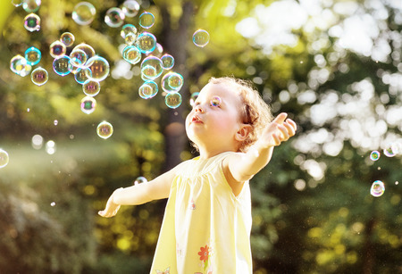Little girl blowing soap bubbles in the summer park