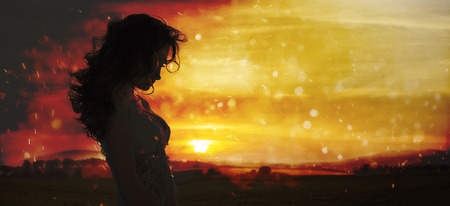 woman sunset: Silhouette of a young woman watching the sunset Stock Photo