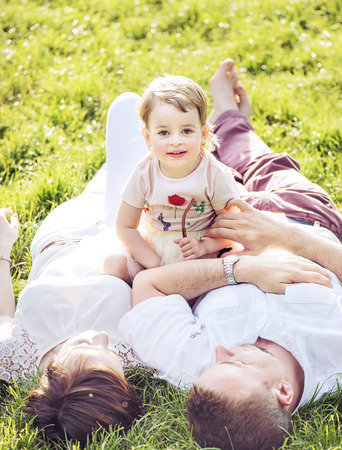 family in park: Pleased family relaxing in a summer park Stock Photo