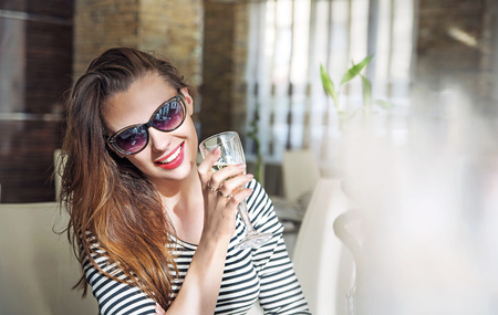 Closeup portrait of a young female customer drinking a glass of white wine