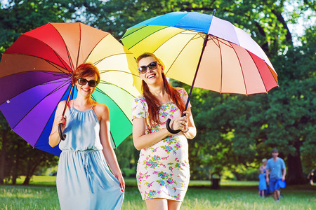 Two fashionable young ladies posing with colorful umbrellas