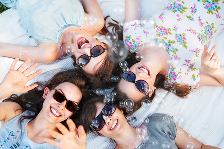 four people: Four attractive ladies blowing tiny soap bubbles Stock Photo