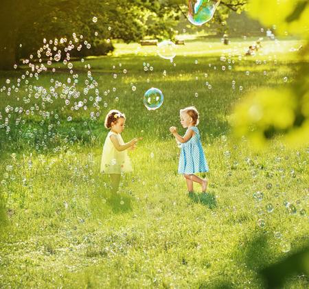 Little girls blowing soap bubbles on a summer, fresh meadow