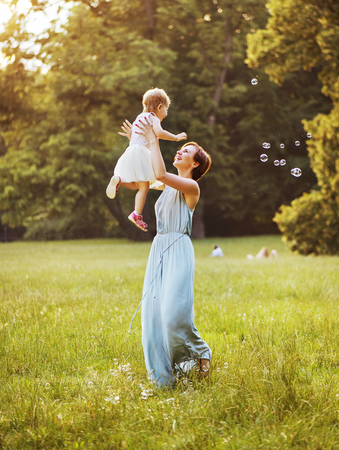 Delighted young mother tossing her lovely child