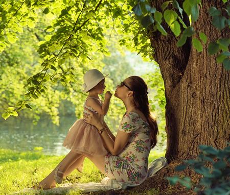 Brunette mother cuddling and kissing her beloved daughter 写真素材
