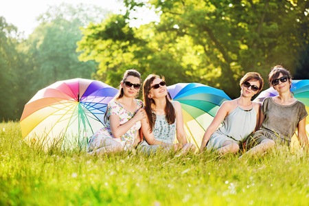 Four attractive ladies sitting on the fresh meadow Stock Photo