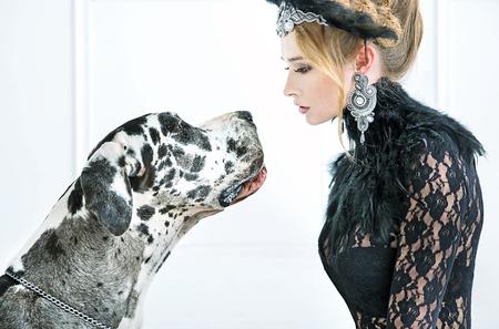 Giovane donna elegante a fissare il cane amichevole photo