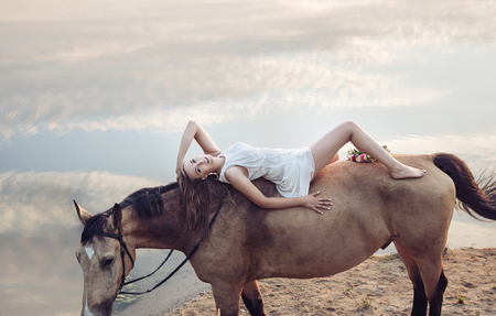 nude model: Portrait of a blond beautiful woman lying on the horse