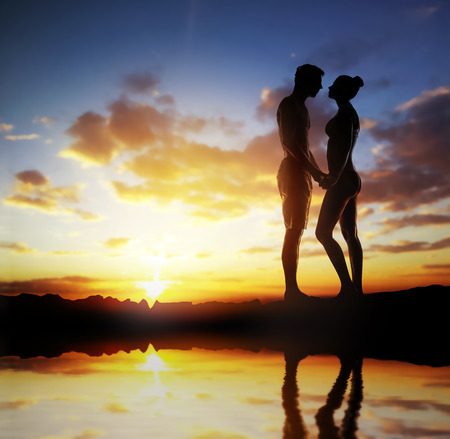 Silhouette of a loving couple over sunset the background