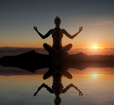 trouble free: Silhouette of a young meditating woman Stock Photo