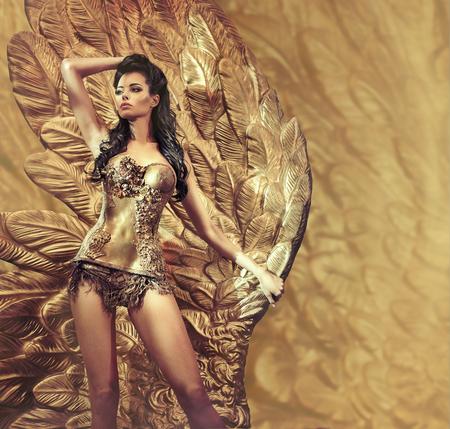 Verleidelijke brunette dame met een enorme gouden vleugel Stockfoto