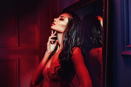 빨간색 장소에 매혹적인 갈색 머리 아가씨 스톡 콘텐츠