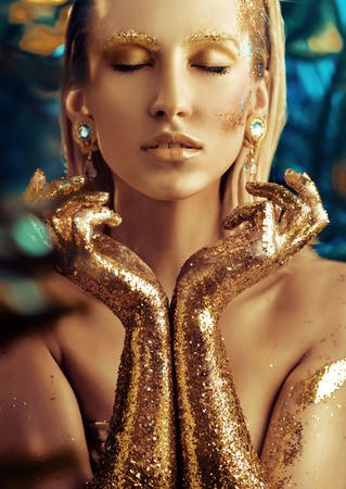 Conceptual portrait of a glittering golden woman 版權商用圖片