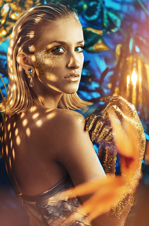 Alluring blond woman with golden, glittering dust on her body