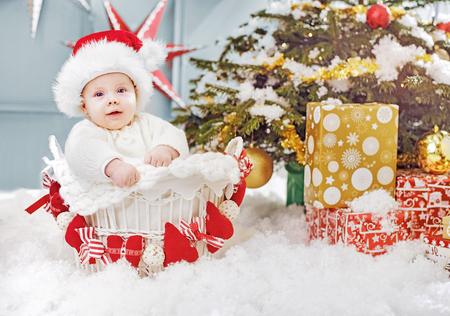 Cute little santa boy sitting in the wicker basket