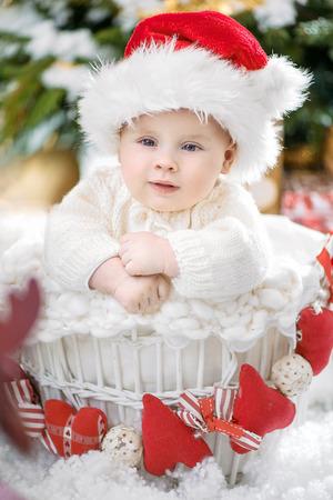 Relaxed little santa boy sitting in the wicker basket
