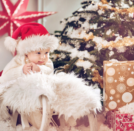 Cute little son looking at the Christmas gifts Stock Photo