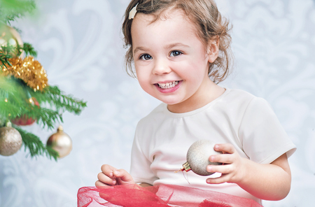 Portrait of a litle girl decorating a fresh Christmas tree Stock Photo