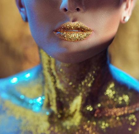 golden: Pretty young woman with golden lips Stock Photo