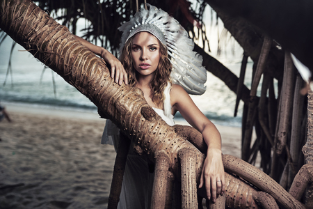Beautiful woman with a plume leaning against the huge branch