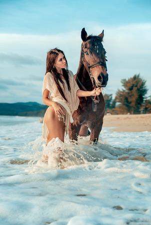 Portret van een aantrekkelijke vrouw die met een Arabisch paard loopt