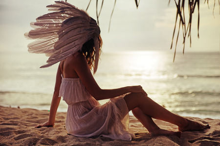 Blond woman with a huge, white plume watching the sunset Stock Photo