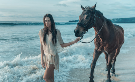 Charming youn glady with a majestic arab horse