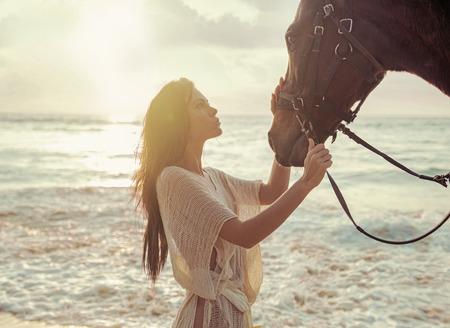 yegua: Mujer encantadora acariciando a su querido amigo caballo