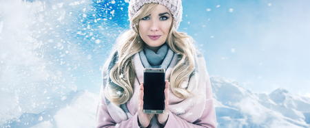 xmas background: Pretty blonde holding a mobile phone, winter bacgkround Stock Photo