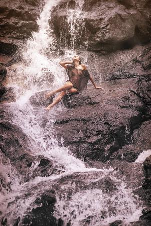 Donna abbastanza bionda sotto la cascata Archivio Fotografico